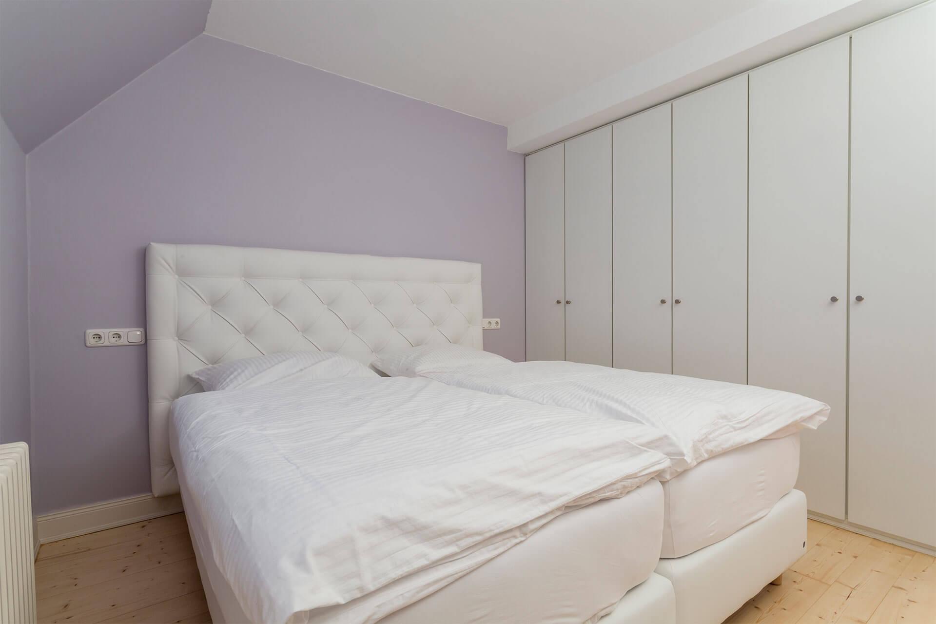 Schlafzimmer mit Boxspringbett mit kuscheliger Betwäsche und Einbauschrank