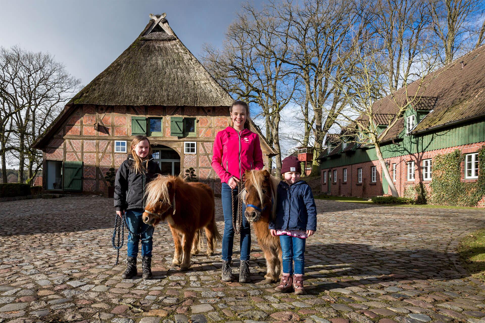 Kinder und Jugendliche mit Shetlandponys auf dem Heinshof vor den Ferienwohnungen
