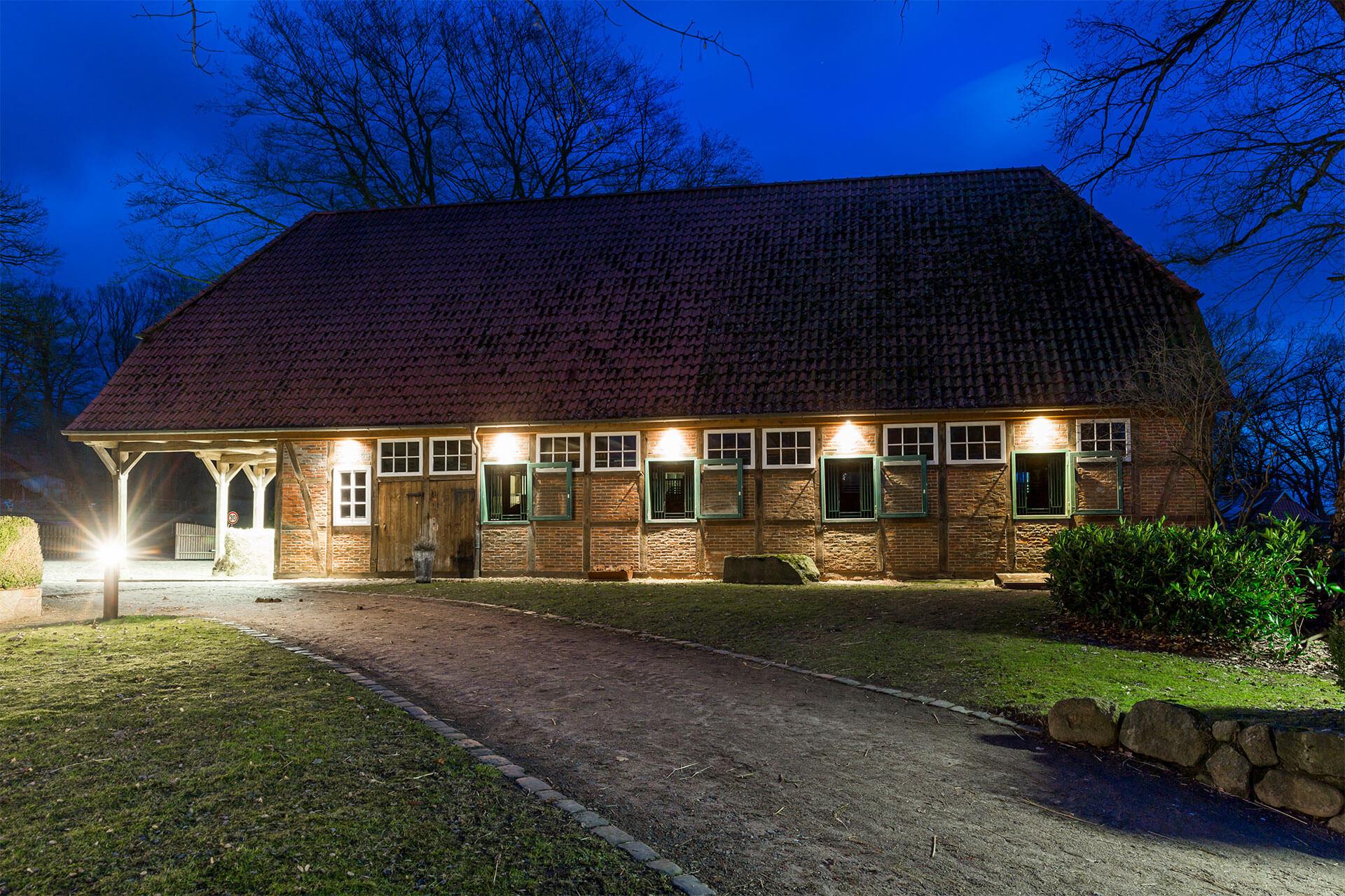 schöner Pferdestall von der Seite mit Blick auf die großen Fensterboxen am Abend