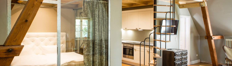 Blick über Esstisch in Küche und Schlafzimmer