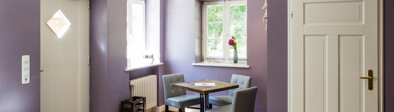 Estisch mit drei Stühlen und zwei Fenstern zur Hofstelle