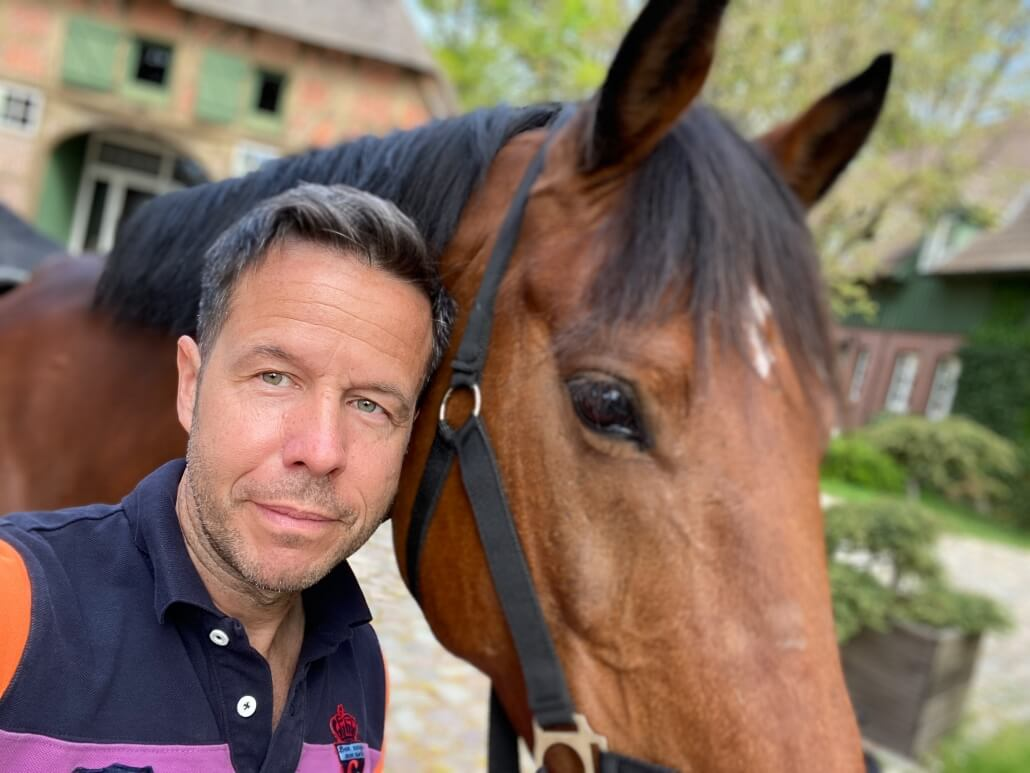 Reiter steht am Pferd